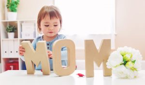small child with MOM letter cutouts
