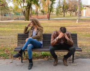 woman and man unhappy sitting on bench