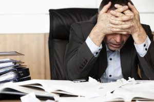 stressed man with hands on face at desk covered in papers