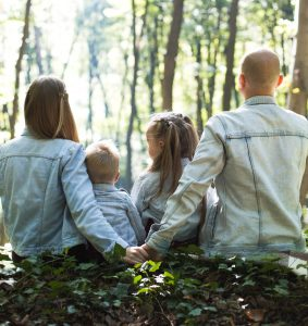 husband and wife with 2 children in the woods